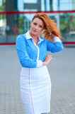 Business woman with red hair in front of office building. Royalty Free Stock Photography
