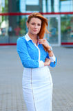 Business woman with red hair in front of office building. Stock Image