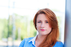 Business woman with red hair in front of office building. Royalty Free Stock Images