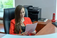 Business woman in red suit sits in a leather chair and reading a contract, checking the paper. Business woman in red suit sits in a leather chair and reading a Royalty Free Stock Photo