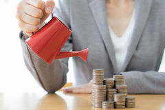 Business woman and red watering can with money Stock Photos