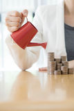 Business woman and red watering can with money Royalty Free Stock Image