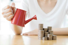 Business woman and red watering can with money Royalty Free Stock Photos