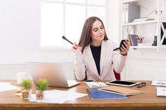 Business woman refreshing her makeup at office Royalty Free Stock Image