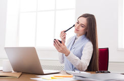 Business woman refreshing her makeup at office Stock Photos