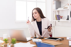 Business woman refreshing her makeup at office Royalty Free Stock Images