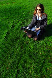 Business woman relaxing. Beautiful young businesswoman relaxing and working in the grass Stock Photos