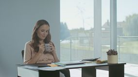 Business woman relaxing with coffee. Tired lady sitting with laptop computer. Business woman relaxing with coffee in luxury house. Tired lady sitting with stock footage