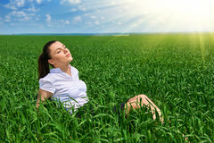 Business woman relaxing in green grass field outdoor under sun. Beautiful young girl dressed in suit resting, spring landscape, br Royalty Free Stock Images