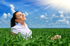 Business woman relaxing in green grass field outdoor under sun. Beautiful young girl dressed in suit resting, spring landscape, br Royalty Free Stock Photos