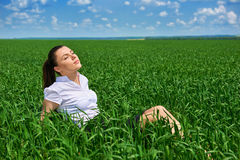 Business woman relaxing in green grass field outdoor under sun. Beautiful young girl dressed in suit resting, spring landscape, br Stock Images