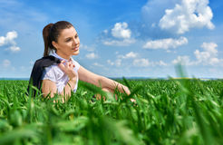 Business woman relaxing in green grass field outdoor under sun. Beautiful young girl dressed in suit resting, spring landscape, br. Ight sunny day Royalty Free Stock Photography