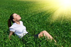 Business woman relaxing in green grass field outdoor under sun. Beautiful young girl dressed in suit resting, spring landscape, br Stock Image
