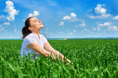 Business woman relaxing in green grass field outdoor under sun. Beautiful young girl dressed in suit resting, spring landscape, br Stock Photo