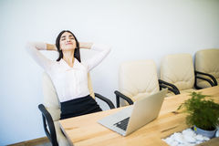Business woman relaxing with hands behind her head and sitting on an office chair Stock Photos