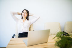 Business woman relaxing with hands behind her head and sitting on an office chair Royalty Free Stock Image