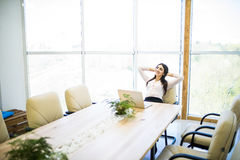 Business woman relaxing with hands behind her head and sitting on an office chair Stock Image