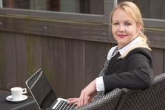 Business woman relaxing with laptop and cup of coffee outdoors Royalty Free Stock Image
