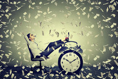 Business woman relaxing sitting in her office under money rain Royalty Free Stock Images