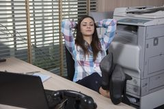 A business woman is relaxing at work. Woman in the  office situation Royalty Free Stock Photography