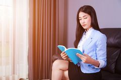 Business woman rests at the sofa and reading a book Stock Photos