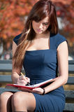 Business woman reviewing diary at city park Stock Image