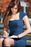 Business woman reviewing diary at city park Royalty Free Stock Photo