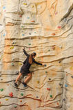 Business woman on rock wall Stock Images