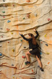 Business woman on rock wall Stock Image