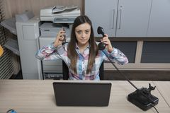 Business woman runs two talks at one time. Office situation Royalty Free Stock Image