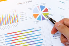 Business woman`s hand checking the results on paperwork. Stock Photo