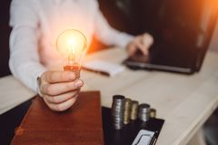 Business woman`s hand holding light bulb with using notebook and notebook and money stack. Idea saving energy and accounting stock photos