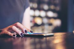 A business woman`s hand touching and sliding finger on smart phone. In modern cafe royalty free stock photography