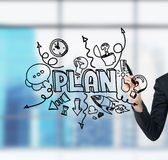 A business woman's hand which is drawing a business plan development sketch on the glass screen. A modern panoramic office in blur Royalty Free Stock Images