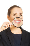 Business woman's teeth through magnyfying glass. Stock Photos