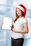 Business woman in Santa Claus hat holds clipboard Stock Image