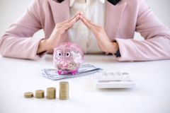 Business woman saving coins into piggy bank and using calculator. To analysis business investment strategy with income of money coin and dollar, financial Stock Images
