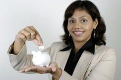 Business woman saving money. Indian business woman putting money in piggy bank, saving money Stock Photography