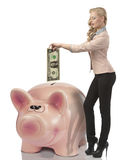 Business woman saving one dollar in a pink bank. Pretty blonde business woman savings one dollar money and putting them in big piggybank. She wearing elegant Stock Photo