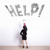 Business woman screaming help. Business woman talking in megaphone with help text on white wall background Royalty Free Stock Photo