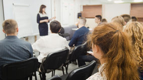 Business woman at seminar - speaker female teaching at international conference, de-focused shot royalty free stock photography