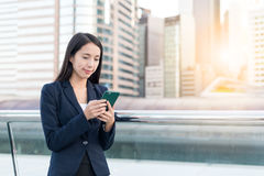 Business Woman sending sms on mobile phone in city. Asian young woman Stock Image