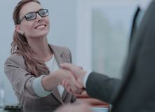 Happy business partners shaking hands in an office Stock Image