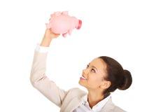 Business woman shaking piggybank. Stock Photos