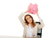 Business woman shaking a piggybank. Stock Image