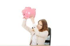 Business woman shaking a piggybank. Stock Photo