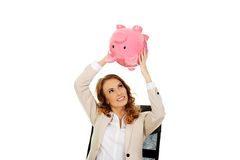 Business woman shaking a piggybank. Stock Image