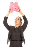 Business woman shaking a piggybank. Stock Images