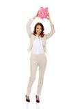 Business woman shaking a piggybank. stock images