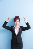 Business woman show something. Business woman is smile and show something to you with on blue background, asian stock image